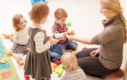 Games in kindergarten. Children with teacher in kindergarten playing cooks royalty free stock photos