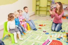 Games in kindergarten. Children with teacher in kindergarten sitting on the chairs a row. Education lesson stock images