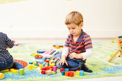 Games at the kindergarten. Cute children play in the kindergarten. A little boy is interested in the toy of his friend royalty free stock photo