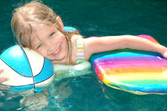 Games in the Pool. Little girl holds onto a basketball for water sports and a kick board used for play and fun royalty free stock images