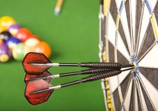 Games room. Three darts in a dart board with a pool game in the background, games room stock photo
