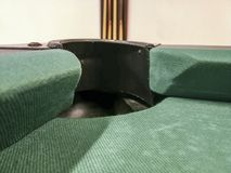 Hole of a billiard table with green cloth and on the background the billiard cues. In a games room of many residences or Italian hotels you will find table royalty free stock photo