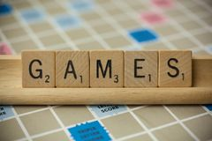 Games Scrabble Tiles. WOODBRIDGE, NEW JERSEY - November 9, 2018: Scrabble tiles spell out the word games on a vintage game board stock photography