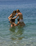 Games at sea 1. Four cute  sisters (best friends) happy and smiling standing in the sea (piggy back) - spend summer holidays (have a fun and games)  in the clear Stock Image