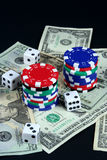 Gaming. Stacks of chips and dice on a pile of money Stock Images