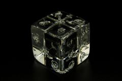 A gaming dice made of glass on a black background, to accentuate transparency. royalty free stock photography