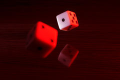 Gaming dice with a red tint. Royalty Free Stock Photos