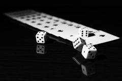 Gaming dice and a row of playing cards. Royalty Free Stock Photo