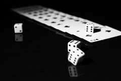 Gaming dice and a row of playing cards. Royalty Free Stock Images