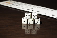 Gaming dice and a row of playing cards. Stock Image