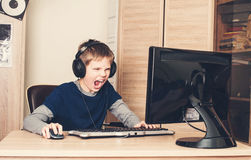 Gaming, entertainment, technology, let`s play concept. Angry scr. Eaming pre teen boy  in headset with pc computer playing game at home Royalty Free Stock Photos