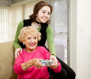 Gaming With Grandma. Teen girl teaching her grandmother how to play video games.  Fun family moment Royalty Free Stock Photo