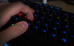 Gaming keyboard with rgb lighting guy having his hand in gaming position stock images