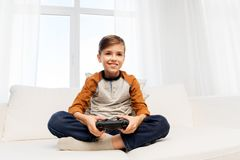 Happy boy with gamepad playing video game at home stock images