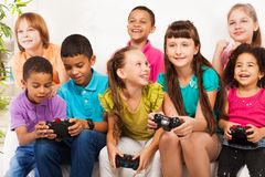 Gaming together. Close portrait of a group of diversity looking kids, boys and girls playing videogame sitting on the sofa holding game controllers, talking and Stock Images