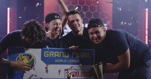 Gaming tournament team celebrating their victory. Medium shot of a gaming tournament team holding their prize while celebrating their victory stock video footage