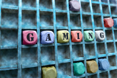 Gaming word made with building wooden blocks. Composition of the word Gaming with wooden cubes in square box / Gaming word made with building wooden blocks stock images