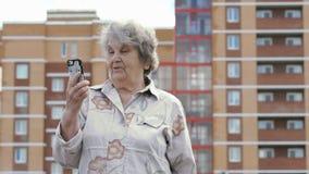 Gamla äldre kvinnasamtal genom att använda den smarta telefonen utomhus arkivfilmer