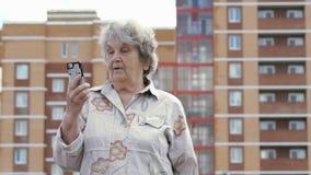 Gamla äldre kvinnasamtal genom att använda den smarta telefonen utomhus stock video