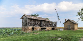 Gamla övergav byggnader och en gammal brunn Arkivbilder