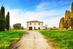 Gamla övergav lantliga hus, väg och träd på solnedgång. Tuscany Italien Royaltyfri Fotografi