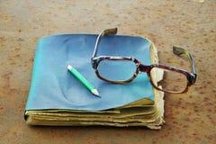 Gamla anteckningsbok, blyertspenna och exponeringsglas Fotografering för Bildbyråer