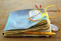 Gamla anteckningsbok, blyertspenna och exponeringsglas Royaltyfri Foto