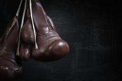 Gamla använda boxninghandskar som hänger för en smutsig vägg Royaltyfri Fotografi