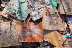 Gamla, använda och brutna chiper för elektronisk strömkrets som kastas i smutsen; bakgrundstexturfoto arkivbild