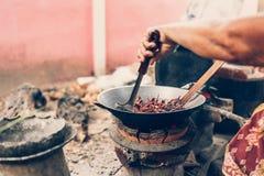 Gamla asiatiska kvinnor grillar torkade r?da chilies i en panna n?ra risspisen royaltyfria bilder