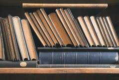 Gamla böcker i ett tappningarkiv Arkivfoto