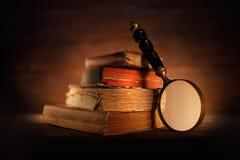 Gamla böcker med det antika förstoringsglaset Arkivbilder