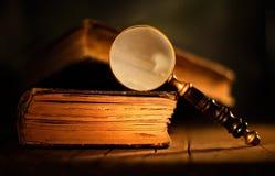 Gamla böcker med det antika förstoringsglaset på trätabellen Royaltyfria Bilder