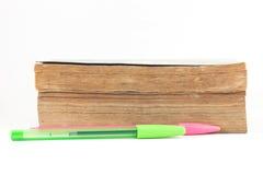 Gamla böcker med några pennor på vit bakgrund Arkivbild