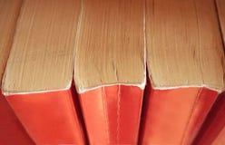 Gamla böcker med rött bokomslag som staplas vertikalt på hyllorna ovanf?r sikt royaltyfri fotografi