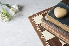Gamla böcker med schackbrädet, blommor och hjärta arkivfoton