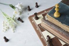 Gamla böcker med schackbrädet arkivfoton