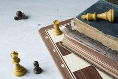 Gamla böcker med schackbrädet fotografering för bildbyråer