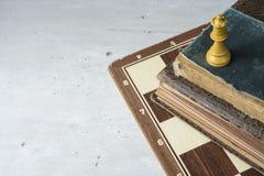 Gamla böcker med schackbrädet, utrymme för text royaltyfri foto