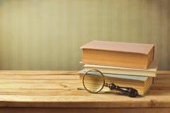Gamla böcker med tappningförstoringsglaset fotografering för bildbyråer