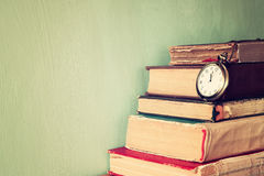 Gamla böcker med tappningrovan på en trätabell retro filtrerad bild Arkivfoto