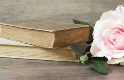 Gamla böcker och blomman steg på en träbakgrund Romantisk blom- rambakgrund Bild av blommor som ligger på en antik bok Royaltyfria Foton
