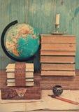 Gamla böcker och jordklot arkivfoton