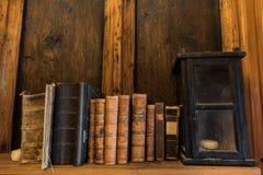 Gamla böcker och lykta på en hylla Arkivbild