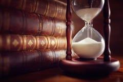 Gamla böcker och timglas Arkivfoto