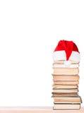 Gamla böcker på hylla i den santa hatten Arkivfoton