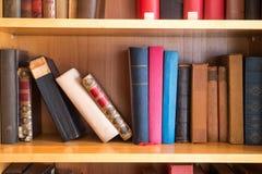 Gamla böcker på hyllor arkivbilder
