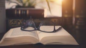 Gamla böcker på skrivbordet med moderna exponeringsglas stock video