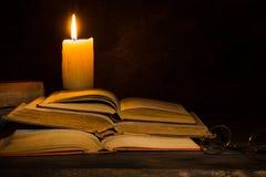 Gamla böcker som läs av stearinljusljus Arkivbild