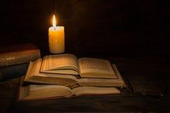 Gamla böcker som läs av stearinljusljus Arkivbilder